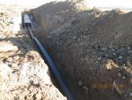 ПК140. Устройство переноса водопровода с нарушениями. Не верно отсыпана постель, негабаритный материал, в траншее грязь (жижа).